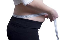 Fat girl measures the size of waist. concept of losing weight. Watch figure. Measuring tape around the waist. A young girl plus size measures her hips. To go stock image