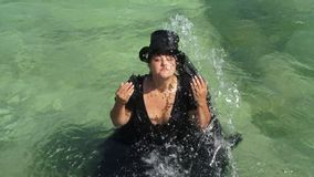 A fat girl is pouring herself with sea water. Slow motion. stock video footage