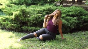 Fat girl in ragged jeans sits on the grass in park. A fat girl with excess weight in ragged jeans and a vest sits on the grass in the park stock video footage
