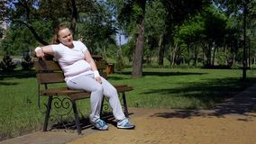 Fat girl sitting on bench, tired after workout in park, lack of motivation royalty free stock photos