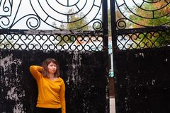 Fat girl standing at the iron gate. The fat girl standing at the iron gate stock image