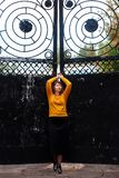 Fat girl standing at the iron gate. The fat girl standing at the iron gate royalty free stock image