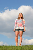 Fat girl stands at green grass and laughs royalty free stock images