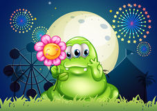 A fat green monster holding a flower at the carnival with a fire Royalty Free Stock Photography