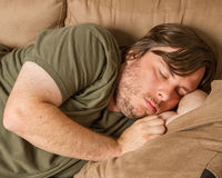 Fat guy asleep on the couch. Passed out drunk, or just a couch potato. You decide Stock Photography