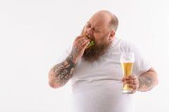 Fat guy biting unhealthy sandwich Stock Photography
