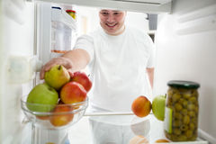 Fat guy on a diet. Taking fruit from refrigerator royalty free stock photography