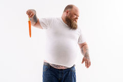 Fat guy does not like carrot Royalty Free Stock Photo