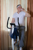 Fat guy exercising on stationary training bicycle and drinking water. At home stock photography