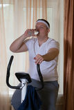 Fat guy exercising on stationary training bicycle and drinking water. At home royalty free stock photos