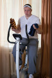 Fat guy exercising on stationary training bicycle and eating a bun. At home royalty free stock photography