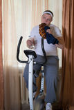 Fat guy exercising on stationary training bicycle and eating a bun. At home royalty free stock images