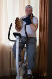 Fat guy exercising on stationary training bicycle and eating a bun. At home royalty free stock image