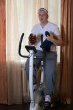 Fat guy exercising on stationary training bicycle and eating a bun. At home stock images