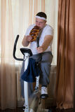 Fat guy exercising on stationary training bicycle and eating a bun. At home stock photography