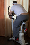 Fat guy exercising on stationary training bicycle. At home stock image