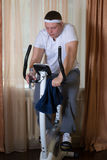 Fat guy exercising on stationary training bicycle. At home stock photos