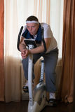Fat guy exercising on stationary training bicycle. At home stock images