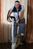 Fat guy exercising on stationary training bicycle. At home stock photo