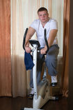 Fat guy exercising on stationary training bicycle. At home royalty free stock images
