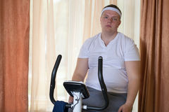Fat guy exercising on stationary training bicycle. At home stock photography
