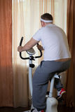 Fat guy exercising on stationary training bicycle. At home royalty free stock photo