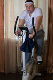 Fat guy exercising on stationary training bicycle. At home royalty free stock image