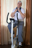 Fat guy exercising on stationary training bicycle. At home royalty free stock photography
