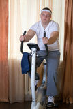 Fat guy exercising on stationary training bicycle. At home royalty free stock photos