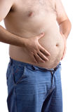 Fat guy holding his big belly. Against white background royalty free stock image