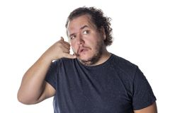 Fat handsome guy showing call me sign. Man in casual keeping hand at ear and imitating phone talk. Fat handsome guy showing call me sign. Man in casual keeping royalty free stock images