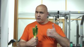 Fat handsome man in orange t-shirt holding leek motivates to do sports stock video