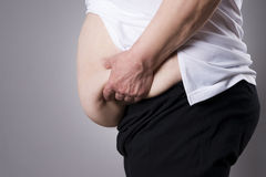 Fat human body. Fatty belly closeup. On gray background Stock Photo