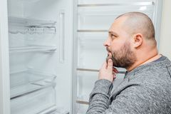 Fat hungry man is looking for a food into empty fridge Royalty Free Stock Image
