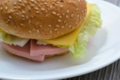 Fat junk fat food unhealthy eating tasty homemade sandwich dieting weight loss Close up photo of tasty appetising cheeseburger wit. H ham and salad on white Royalty Free Stock Photo
