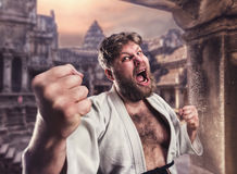 Fat karate fighter. Aggressive bearded karate fighter in white kimono in the temple stock photo