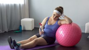 Fat lady depressed about her weight unsuccessful workout restoring water balance. Stock photo royalty free stock photography