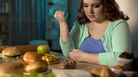 Fat lady exercising with dumbbell and looking at sweet donut, dieting willpower. Stock photo royalty free stock photos