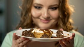 Fat lady looking with admiration at plate with sweets and candies food addiction. Stock photo royalty free stock images