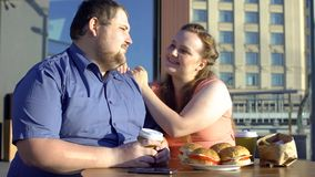 Fat lady looking with love at obese boyfriend, true feelings, fast food concept. Stock photo stock images