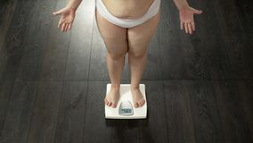Fat lady measuring weight on scales, angry with result, unsuccessful dieting. Stock photo royalty free stock images