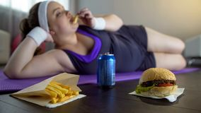Fat lazy girl in sportswear eating junk food instead of training on yoga mat royalty free stock photo
