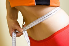 Fat loss concept - slim waist and measure tape Royalty Free Stock Photography