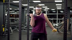 Fat male choosing between healthy lifestyle and fast food, making right choice. Stock photo royalty free stock image