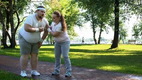 Fat male feels heart pain while jogging, obese girl helping him, friends support stock image