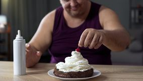 Fat male putting cherry on the top of sweet cake decorated with whipped cream Royalty Free Stock Photo
