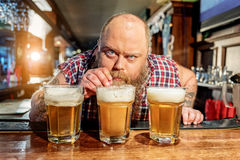Fat male tasting alcohol beverage in dramshop Royalty Free Stock Images