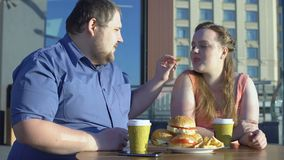 Fat male treating girlfriend with fries couple eating junk food, obesity problem. Stock footage stock footage