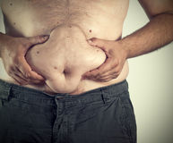 Fat man. Close up of man grabbing his fat on the stomach Royalty Free Stock Photography