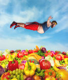Fat man above the fruit and vegetable heap Stock Photo